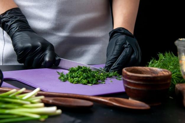 Vooraanzicht vrouwelijke kok die smakelijke salade maakt, snijgroenten op een donkere achtergrond keuken vakantie werk eten maaltijd baan kleur keuken