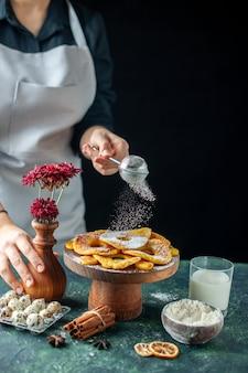 Vooraanzicht vrouwelijke kok die suikerpoeder giet op gedroogde ananasringen op de donkere fruitkokende baan werknemer gebak taart taart bakkerij