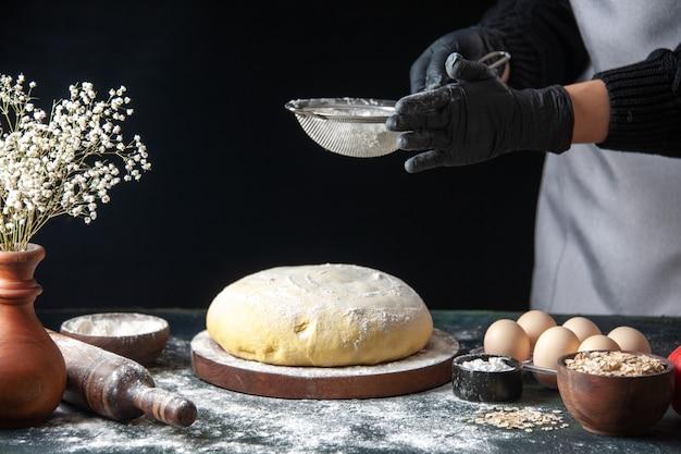 Vooraanzicht vrouwelijke kok die witte bloem giet op rauw deeg op donkere banketbaan rauw deeg hotcake bakkerijoven