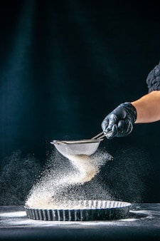 Vooraanzicht vrouwelijke kok die witte bloem in de pan giet op de donkere deeg ei baan bakkerij hotcake gebak keuken keuken