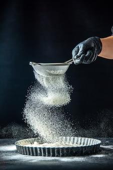 Vooraanzicht vrouwelijke kok die witte bloem in de pan giet op donkere deeg ei baan bakkerij hotcake keuken keuken