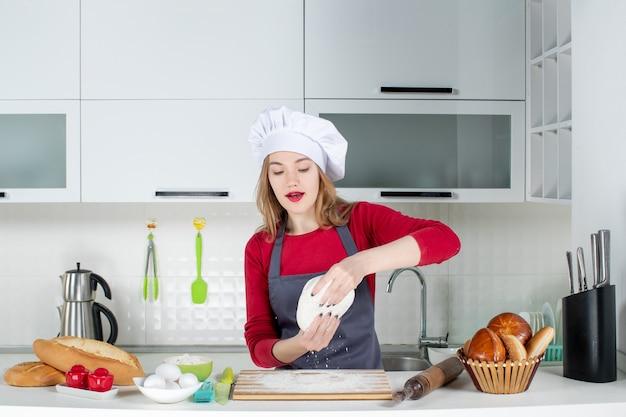Vooraanzicht vrouwelijke kok in koksmuts die deeg in de keuken omhoog houdt