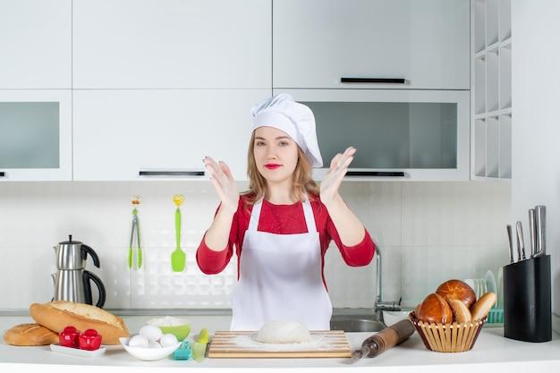 Vooraanzicht vrouwelijke kok in koksmuts en schort die in haar handen klapt in de keuken