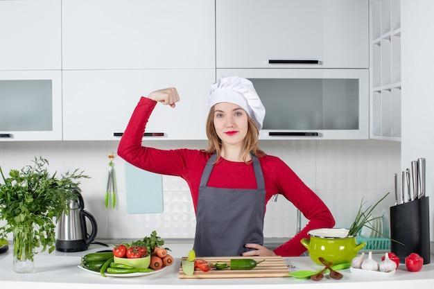 Vooraanzicht vrouwelijke kok in schort die haar wapenspieren toont