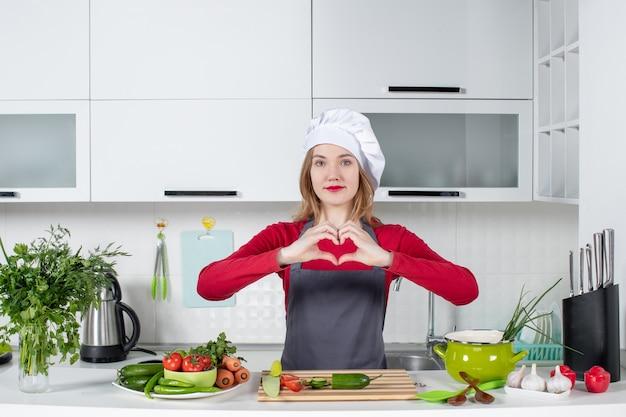 Vooraanzicht vrouwelijke kok in schort die hartteken maakt