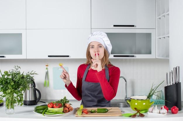 Vooraanzicht vrouwelijke kok in schort die shh-teken maakt