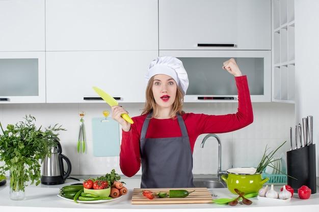 Vooraanzicht vrouwelijke kok in schort met mes die haar kracht toont