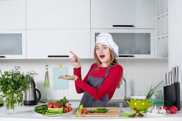 Vooraanzicht vrouwelijke kok in schort wijzend naar links