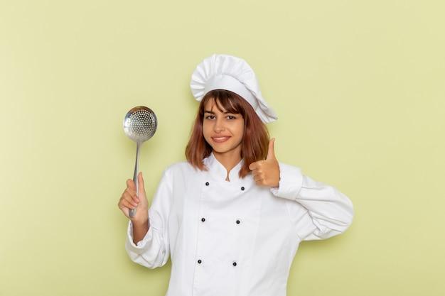 Vooraanzicht vrouwelijke kok in wit kokkostuum die grote zilveren lepel houden die op groene oppervlakte glimlachen