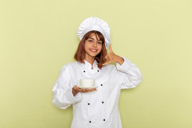 Vooraanzicht vrouwelijke kok in witte kok pak houden kopje thee op groene ondergrond