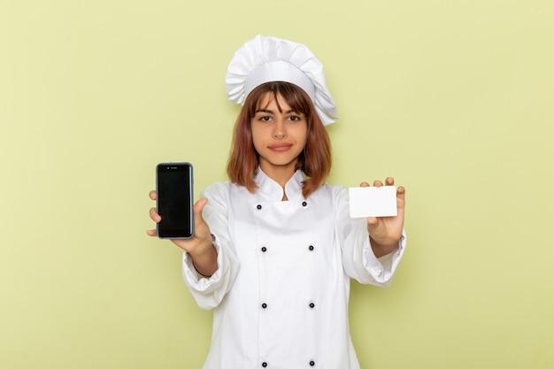 Vooraanzicht vrouwelijke kok in witte kok pak met kaart en smartphone op groene ondergrond