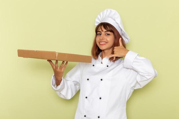 Vooraanzicht vrouwelijke kok in witte kok pak met voedseldoos op groen bureau