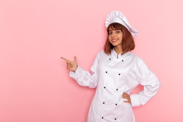 Vooraanzicht vrouwelijke kok in witte kok pak poseren en glimlachen op een roze oppervlak