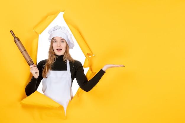 Vooraanzicht vrouwelijke kok met deegroller op gele zon voedselkleur keuken baan keuken foto