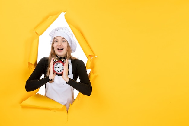 Vooraanzicht vrouwelijke kok met klok op gele foto kleur baan keuken keuken zon eten emoties tijd