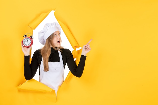Vooraanzicht vrouwelijke kok met klokken op geel voedsel foto kleur baan keuken emotie tijd zon keuken