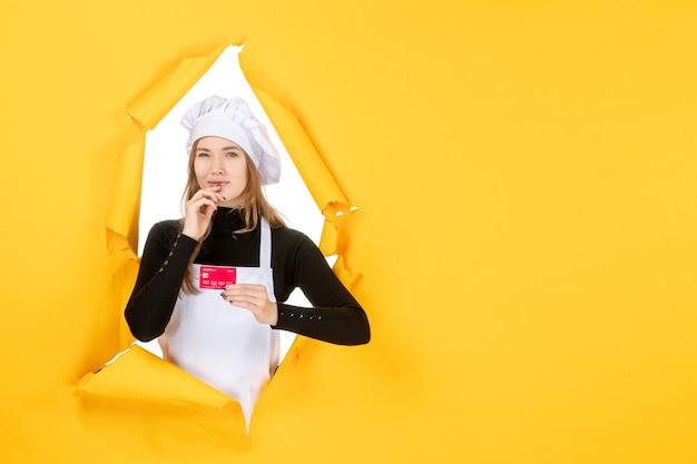 Vooraanzicht vrouwelijke kok met rode bankkaart op gele foto emotie keuken keuken kleur geld baan