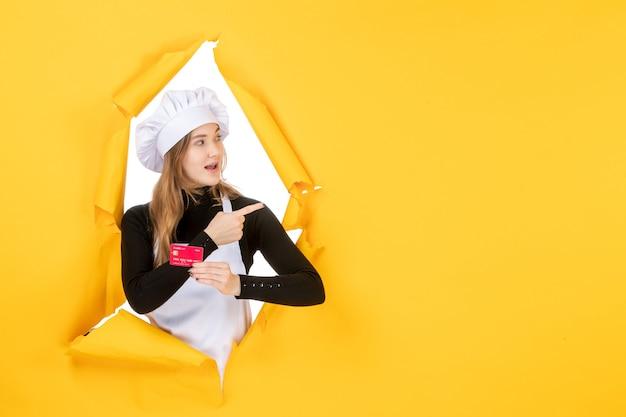 Vooraanzicht vrouwelijke kok met rode bankkaart op gele foto emoties voedsel keuken keuken kleur geld baan