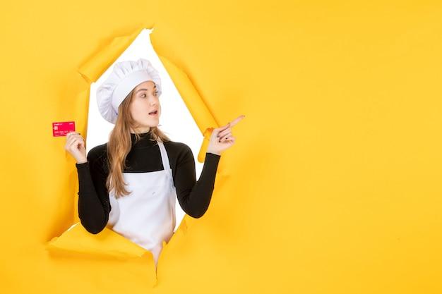 Vooraanzicht vrouwelijke kok met rode bankkaart op gele geldkleur baan foto keuken keuken emotie