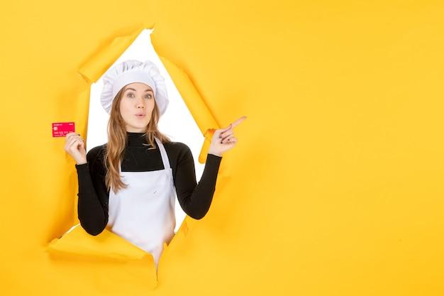 Vooraanzicht vrouwelijke kok met rode bankkaart op gele geldkleur baan voedsel keuken keuken emotie