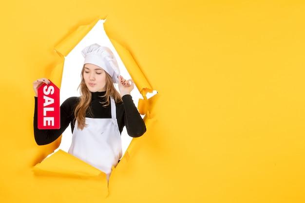 Vooraanzicht vrouwelijke kok met rode verkoop schrijven op een gele voedselkleur keuken emotie foto keuken baan