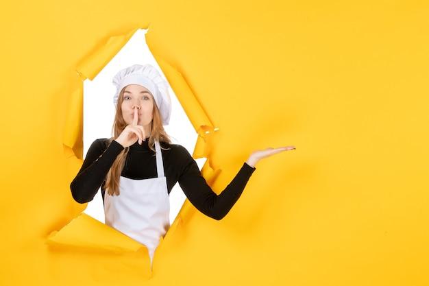 Vooraanzicht vrouwelijke kok vraagt om te zwijgen op gele keuken foto voedsel baan kleur papier zon keuken