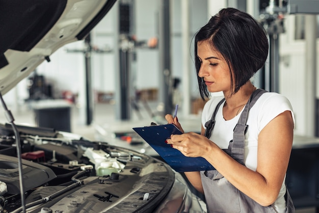 Vooraanzicht vrouwelijke mechanische inspecterende auto