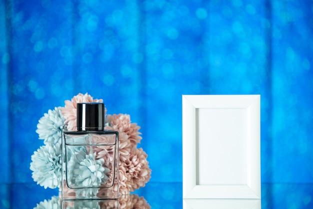 Vooraanzicht vrouwelijke parfum kleine witte fotolijst bloemen op blauwe achtergrond vrije ruimte