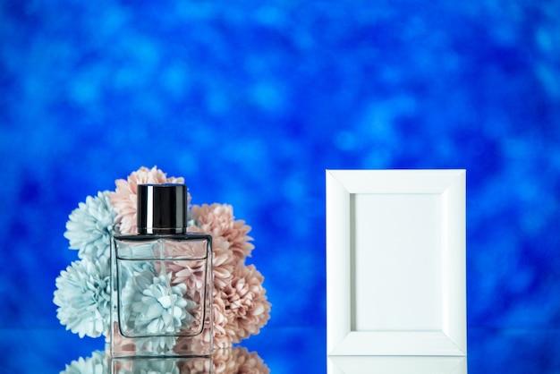 Vooraanzicht vrouwelijke parfum kleine witte fotolijst bloemen op blauwe onscherpe achtergrond met vrije ruimte