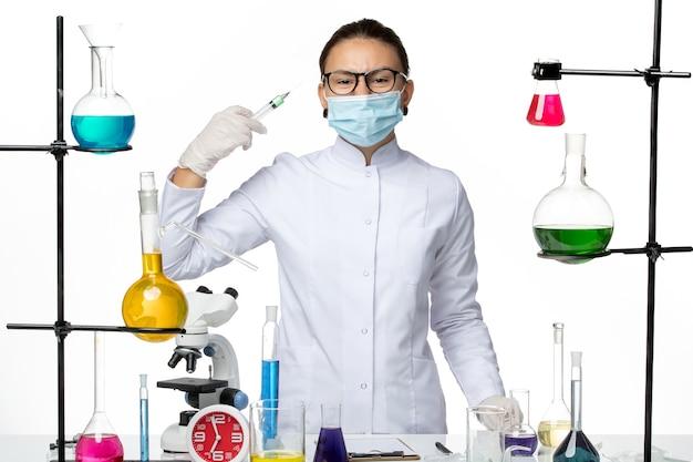 Vooraanzicht vrouwelijke scheikundige in medisch pak met injectie van de maskerholding op lichte witte achtergrond het laboratoriumcovidplons van het viruschemie