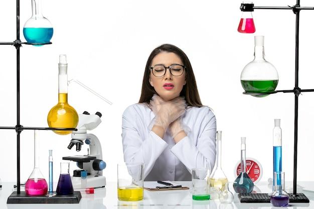 Vooraanzicht vrouwelijke scheikundige in wit medisch pak zichzelf stikken op witte achtergrond wetenschap pandemie virus covid lab
