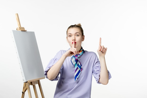Vooraanzicht vrouwelijke schilder met ezel voor het schilderen op witte muur kunst foto kunstenaar verf tekening