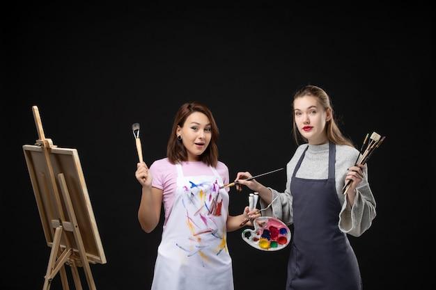 Vooraanzicht vrouwelijke schilders met verf en kwasten om op de zwarte muur te tekenen schilderij werk foto kunst foto kleur kunstenaar