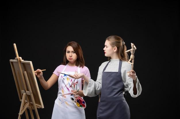 Vooraanzicht vrouwelijke schilders tekenen menselijke figuur op ezel op zwarte muur foto kleur tekenen schilderij baan kunst kunstenaars foto