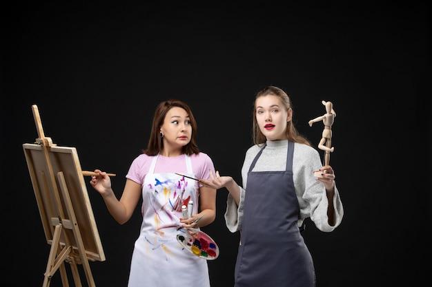 Vooraanzicht vrouwelijke schilders tekenen menselijke figuur op ezel op zwarte muur foto kleuren tekenen schilderij baan kunst kunstenaar foto