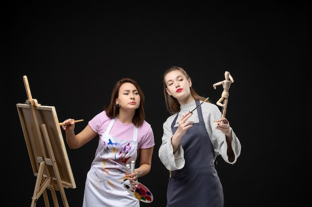 Vooraanzicht vrouwelijke schilders tekenen op ezel op zwarte muur foto kleur tekenen schilderij baan kunst kunstenaar foto