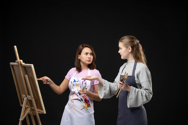 Vooraanzicht vrouwelijke schilders tekenen op ezel op zwarte muur kleur tekenen schilderij baan kunst foto kunstenaar foto's