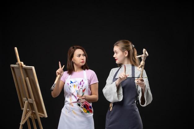 Vooraanzicht vrouwelijke schilders tekening foto van menselijke figuur op ezel op de zwarte muur trekken schilderij art foto art foto kunstenaar kleur job foto