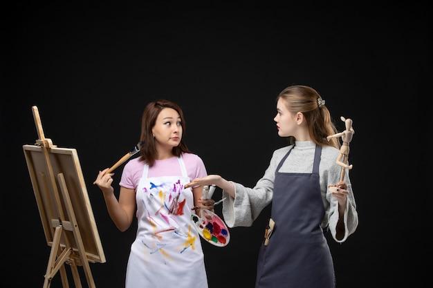 Vooraanzicht vrouwelijke schilders tekening foto van menselijke figuur op ezel op de zwarte muur trekken schilderij art kunstenaar kleur baan foto foto