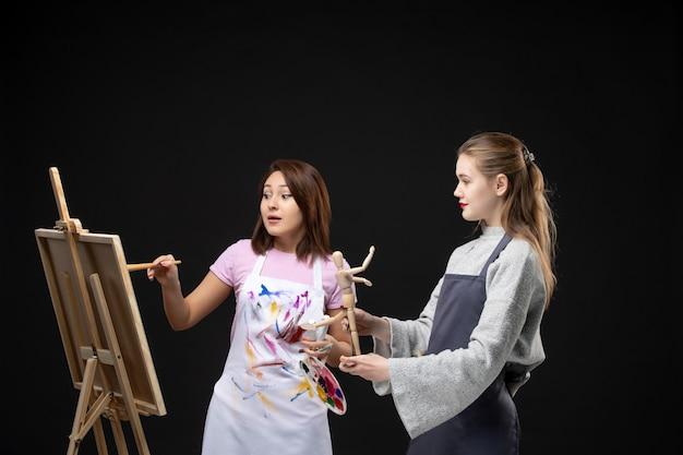 Vooraanzicht vrouwelijke schilders tekening foto van menselijke figuur op ezel op zwarte muur tekenen schilderij kunst kunstenaar kleur baan foto foto's