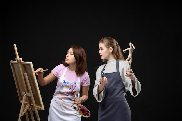 Vooraanzicht vrouwelijke schilders tekening menselijke figuur op ezel op zwarte muur foto kleur tekenen schilderij baan kunst kunstenaar foto