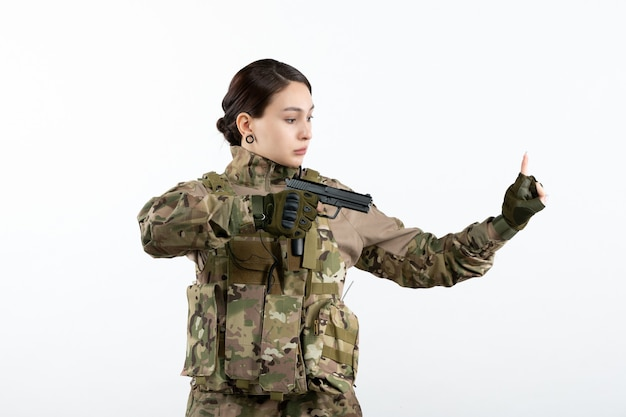 Vooraanzicht vrouwelijke soldaat in camouflage met pistool op witte muur