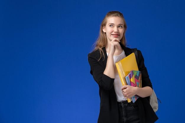 Vooraanzicht vrouwelijke student in wit overhemd en zwart jasje dragen rugzak met bestanden met voorbeeldenboek denken op blauwe muur college universitaire lessen