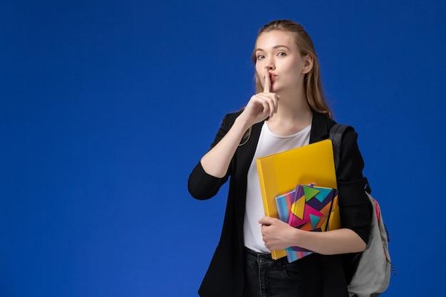 Vooraanzicht vrouwelijke student in wit overhemd en zwart jasje dragen rugzak met bestanden met voorbeeldenboeken op de blauwe muur college universitaire lessen boeken