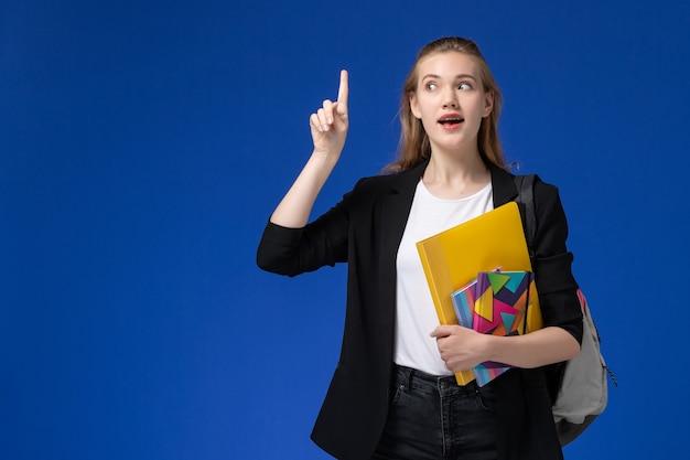 Vooraanzicht vrouwelijke student in zwart jasje dragen rugzak bedrijf bestand met voorbeeldenboeken op blauwe muur boeken college universitaire les