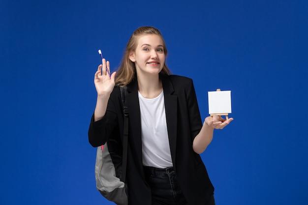 Vooraanzicht vrouwelijke student in zwart jasje dragen rugzak bedrijf ezel lachend op de blauwe muur tekening kunstacademie