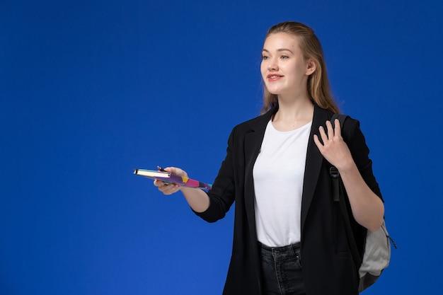 Vooraanzicht vrouwelijke student in zwart jasje dragen rugzak bedrijf pen en voorbeeldenboek op de blauwe muur boek school college universitaire les