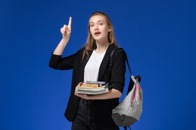 Vooraanzicht vrouwelijke student in zwart jasje dragen rugzak met boeken met opgeheven vinger op de blauwe muur school universiteit college lessen
