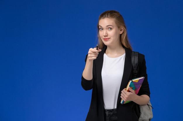 Vooraanzicht vrouwelijke student in zwart jasje dragen rugzak met pen en voorbeeldenboek op de blauwe muur college universitaire lessen