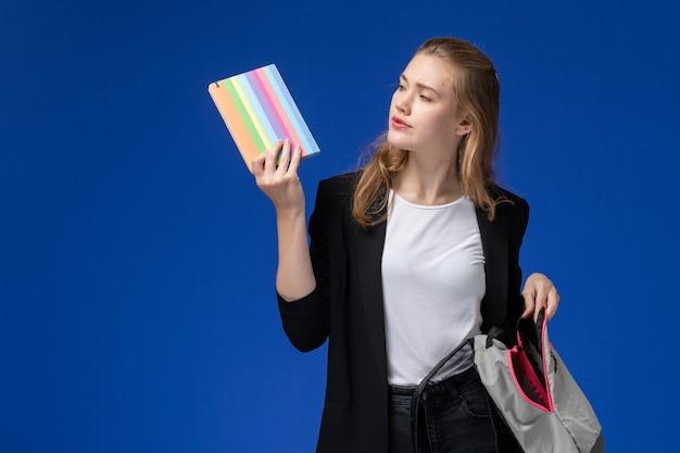 Vooraanzicht vrouwelijke student in zwart jasje met grijze rugzak en voorbeeldenboek op de blauwe muur school college universitaire lessen